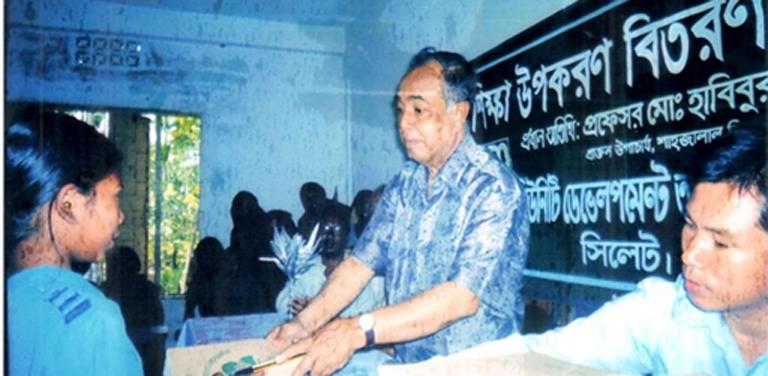 Ex-ECDO adviser and renowned Professor Habibur Rahman is distributing Education Materials among the poor Khasi indigenous students (2005)